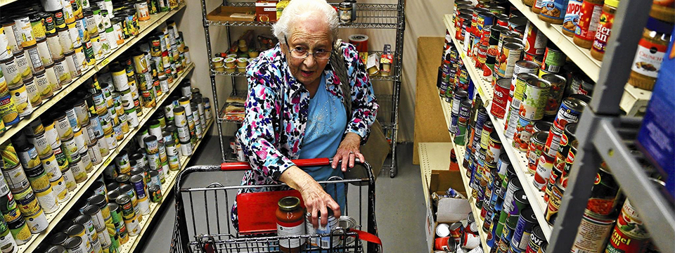 Photo of an elderly woman standing alone putting things into her shopping cart in a grocery store aisle.