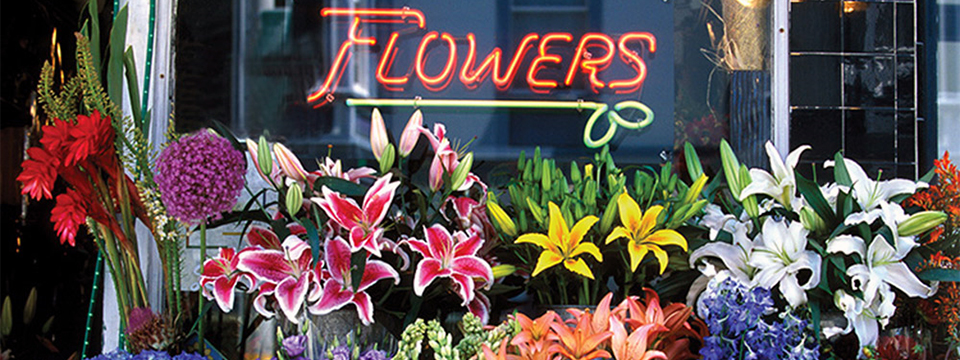 Photo of the front of a Flower Shop with the word 'Flowers' in neon in the window lit up just above rows and rows of flower arrangements.