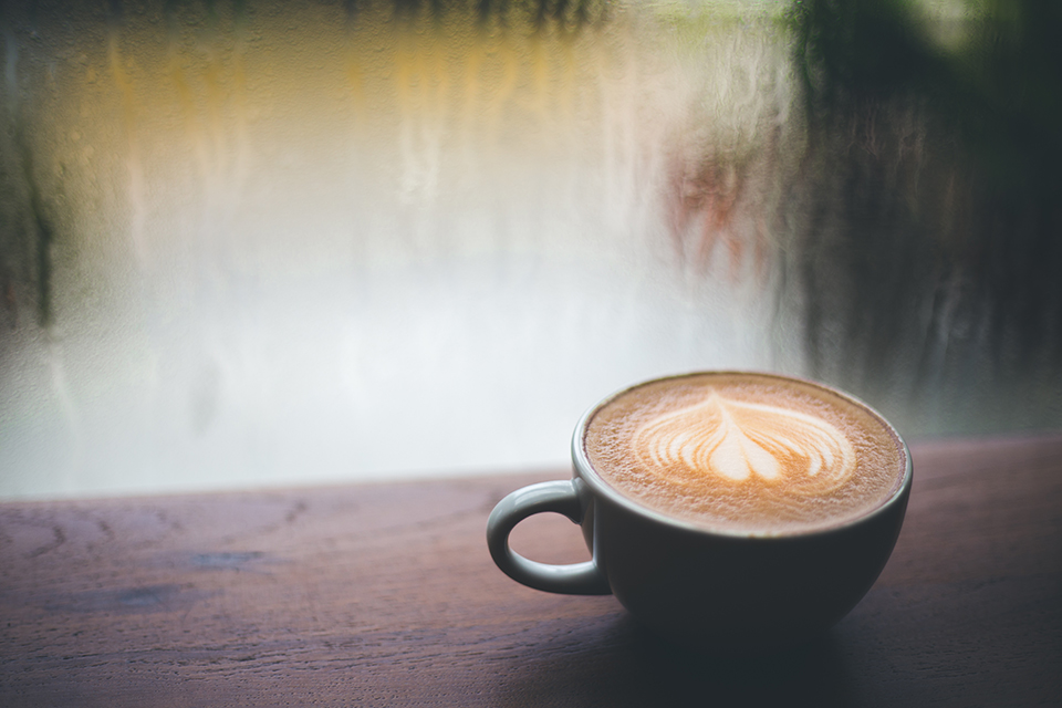 A beautifully frothed coffee latte sits atop a wooden table facing a window streaked from a light rain outside.