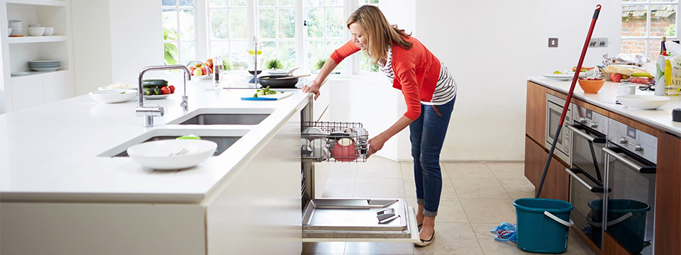 Photo of a woman standing in the middle of a large kitchen cleaning.