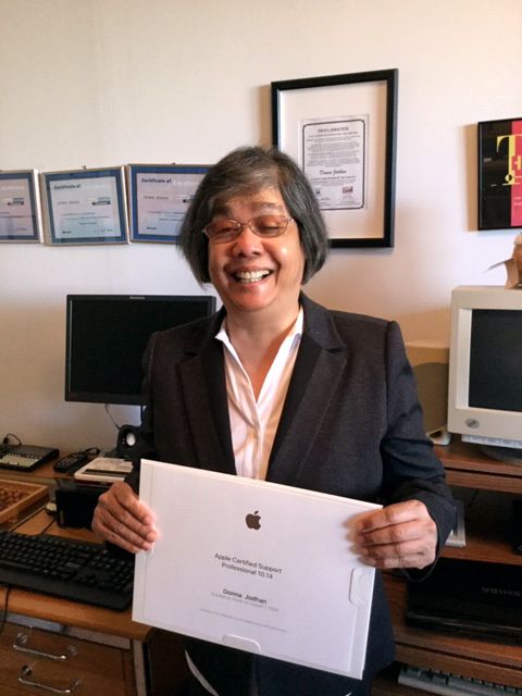 A smiling Donna Jodhan holds her ACSP Certificate.