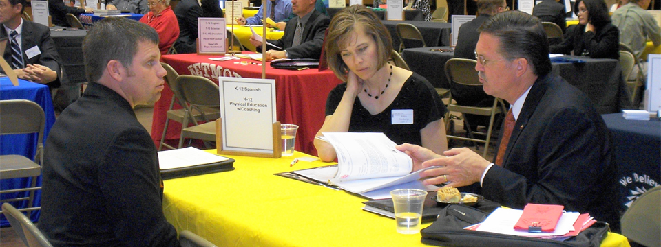 Photo of a man and a woman sitting at a table interviewing another man sitting across the table from them at a job fair.