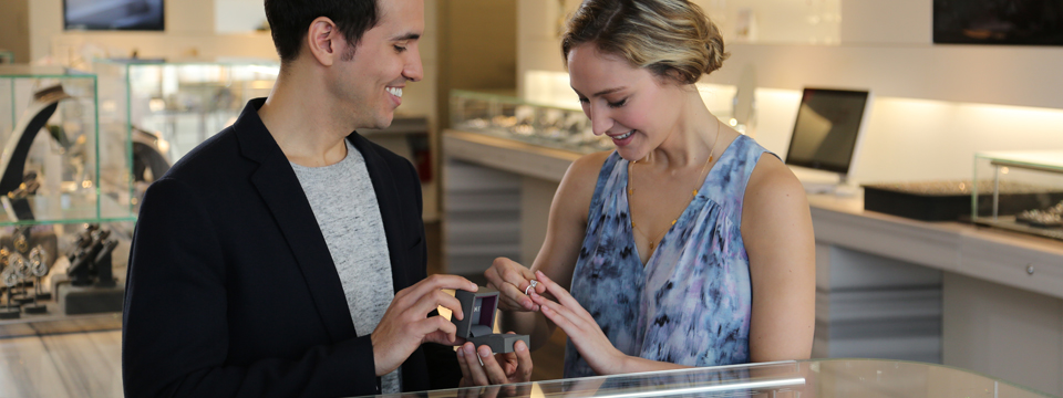 Photo of a very happy man and woman standing in front of a jewelry counter in a department store. The man is holding the box for a ring that the woman is trying on.