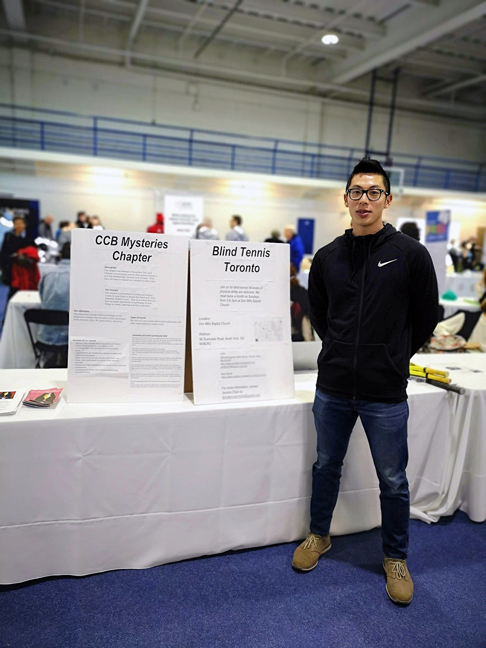 Jerome Chan stands to the right of side by side table placards. On the left the CCB Mysteries Chapter placard. On the right the Blind Tennis Toronto placard. Expo in the background.