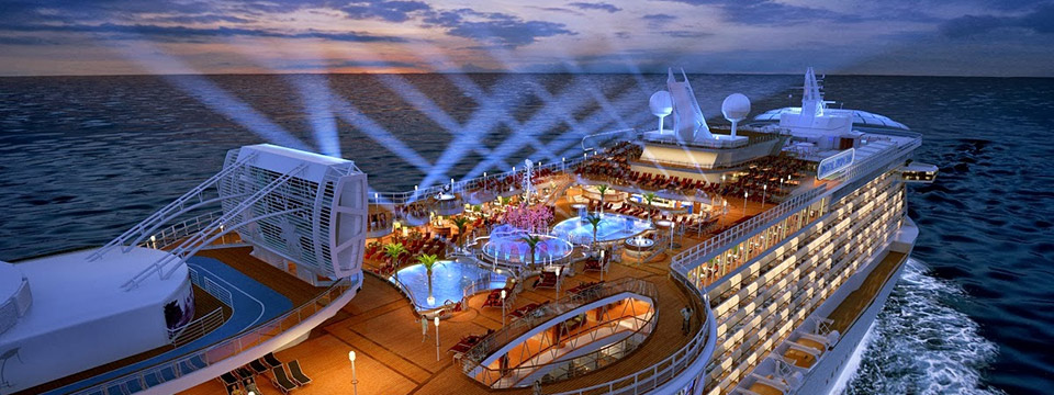Photo of an aerial view of a beautiful luxury cruise ship at dusk. A beautiful array of criss-crossed spotlights shoot into the sky from the top deck.
