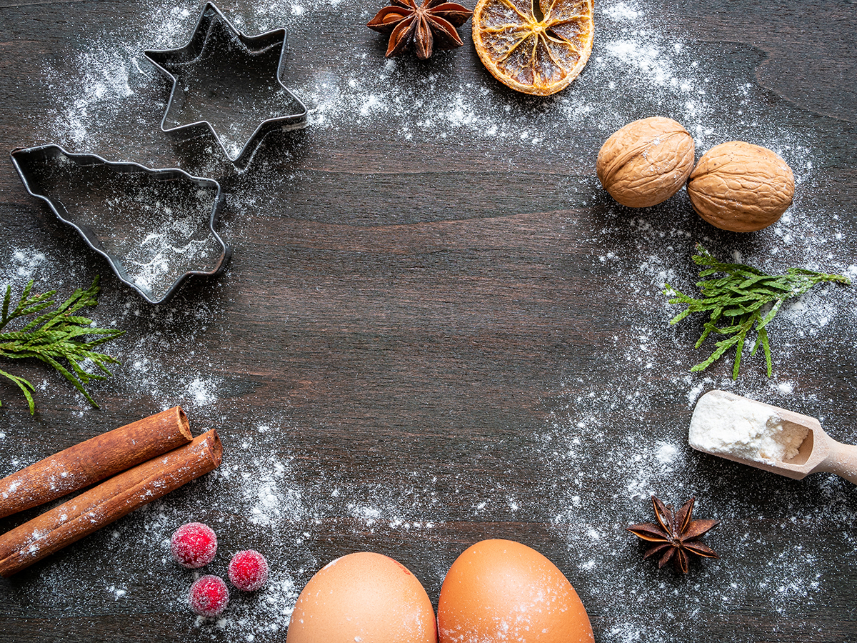 On top of a wooden table covered in sprinkles of white flour are cinnamon sticks, pine fronds, raspberries, star anise, eggs and cookie cutters all arranged in a circle.