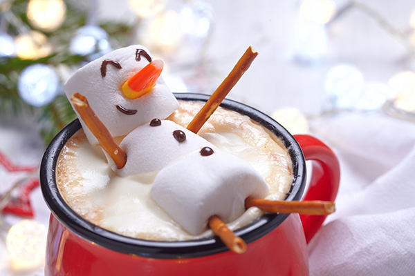 On top of a red mug filled with hot chocolate floats a smiling marshmallow snowman.