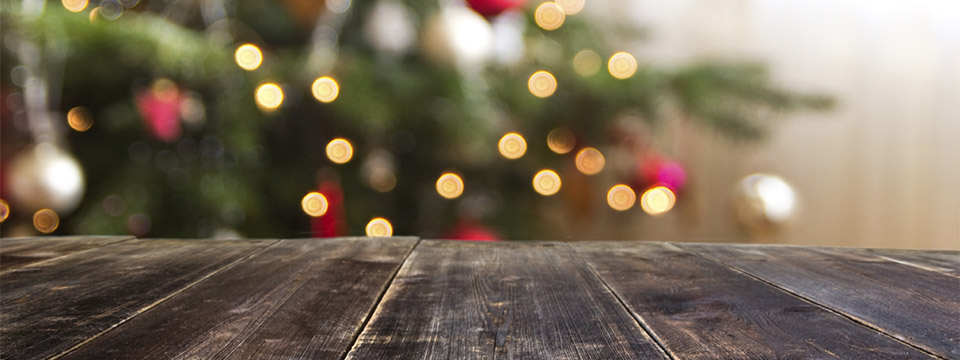 A beautiful thought-provoking photograph looks out across a worn wooden table. In the distance, slightly blurred, is the silhouette of a Christmas Tree full of decorations and lights.