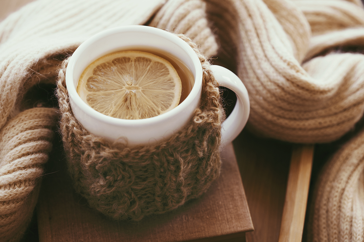 Cup of hot tea with a lemon slice on top dressed in a knitted warm winter scarf on a brown wooden tabletop. Soft focus.