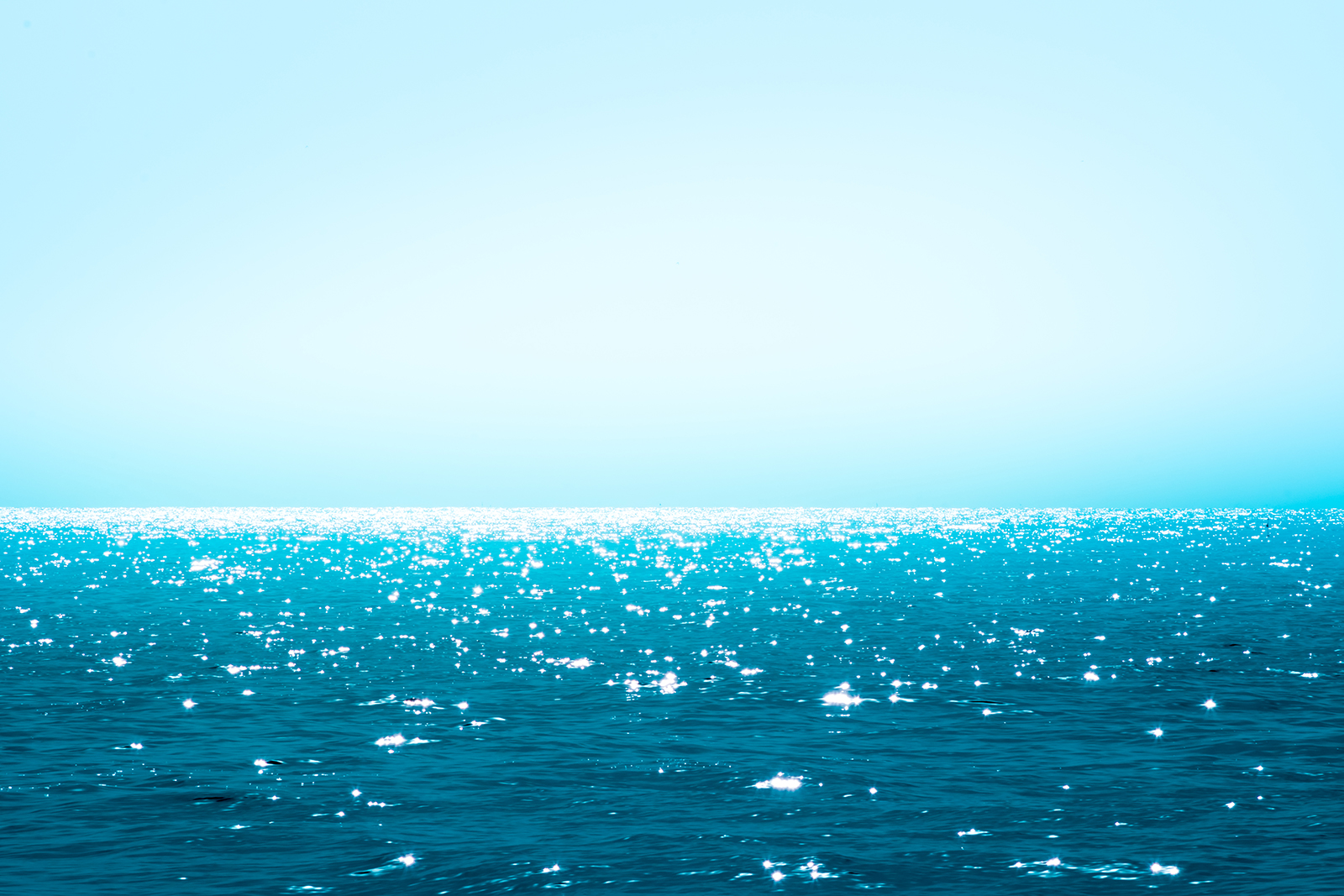 Image. A beautiful deep blue-green ocean sparkles in the sun for as far as the eye can see.