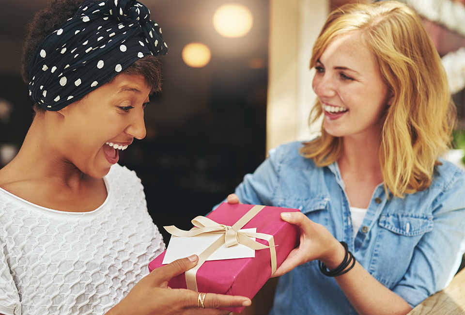 Two women excitedly exchange gifts.