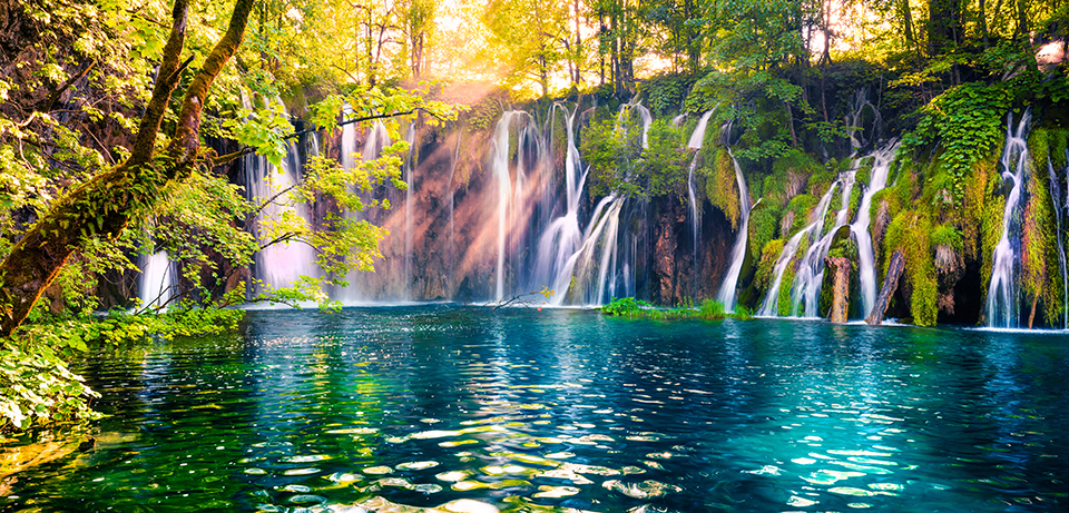 Sunlight sparkles across a stunning blue stream with waterfalls in the background.