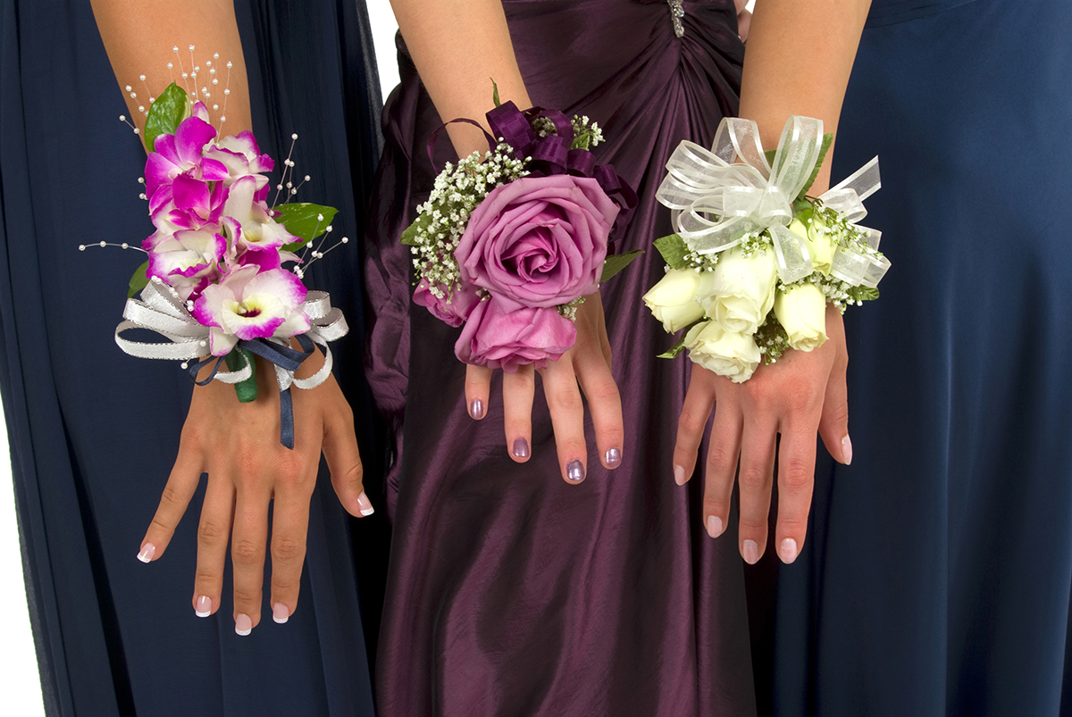 Three women stand together, arms outstretched, each showcasing a different corsage.