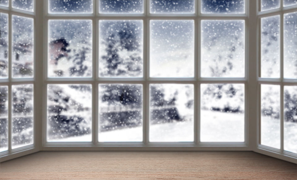 Blurred background of a large picture window with a beautiful winter landscape in the background.