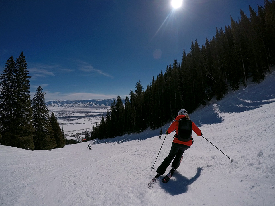 Photo of a woman on skis beginning her descent down a beautiful looking winter slope.