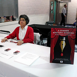 Donna Jodhan smiling while sitting at a table at one of her many Dinner Mystery Evening events.