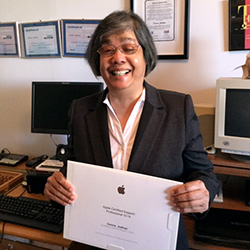 Donna Jodhan smiling while holding her Apple Certified Support Professional (ACSP) Certificate.