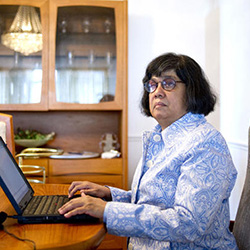 Donna Jodhan sitting at a laptop writing fiction.