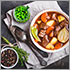 Meat stew with beef, potato, carrot, onion, spices. Green peas. Slow cooked meat stew in bowl, wooden background. Hot autumn/winter dish. Comfort food. Homemade soup/stew.