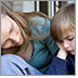 Photo of a mother sitting on the porch steps consoling her young son who appears to be sad.