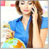 Photo of a woman at a travel agency on the phone with a pencil in her other hand pointing at a globe.