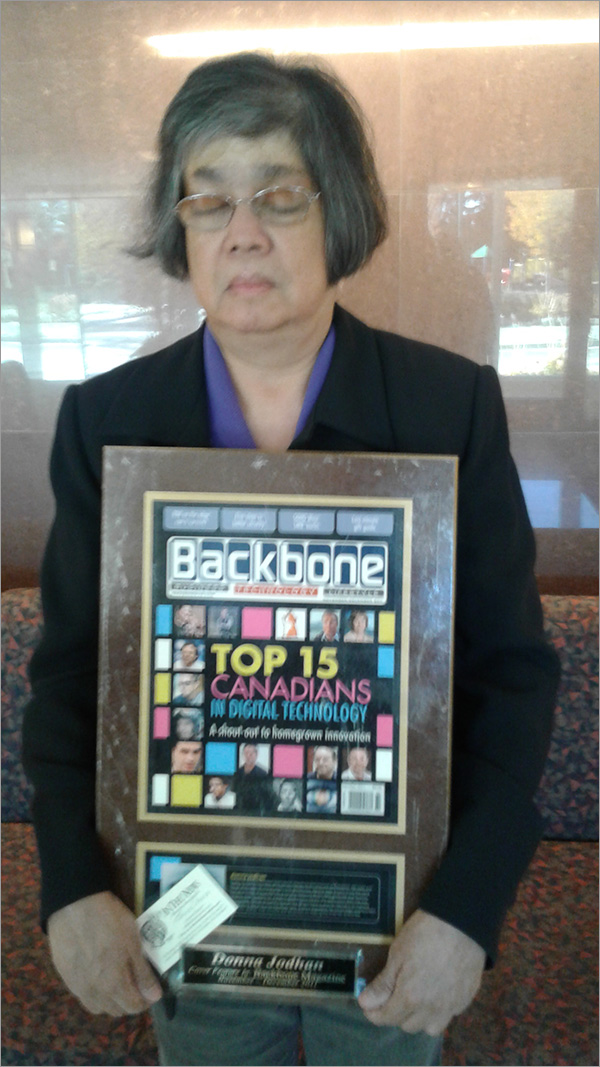 A photo of Donna Jodhan holding the Award presented by Backbone Magazine for being named one of the Top 15 Canadians in Digital Technology.