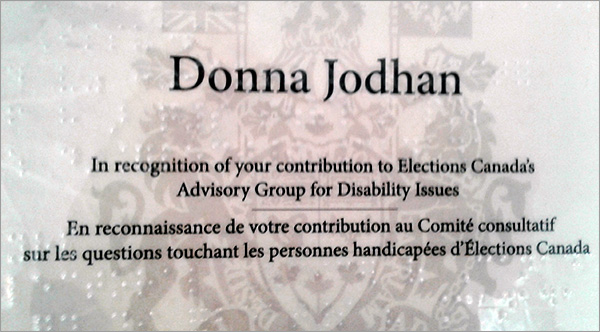 Photo of the award presented by Elections Canada to Donna Jodhan for contributions to Advisory Group for Disability. The award reads, In recognition of your contribution to Elections Canada's Advisory Group for Disability Issues. En reconnaissance de votre contribution au Comite' consultatif sur les questions touchant les personnes handicapees d'Elections Canada.