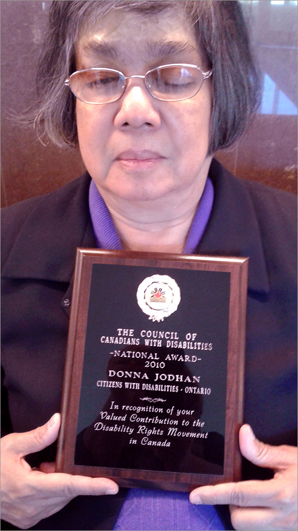 Photo of Donna Jodhan holding the 2010 National Award  presented by The Council of Canadians with Disabilities for Recognition of Valued Contribution to the Disability Rights Movement in Canada.