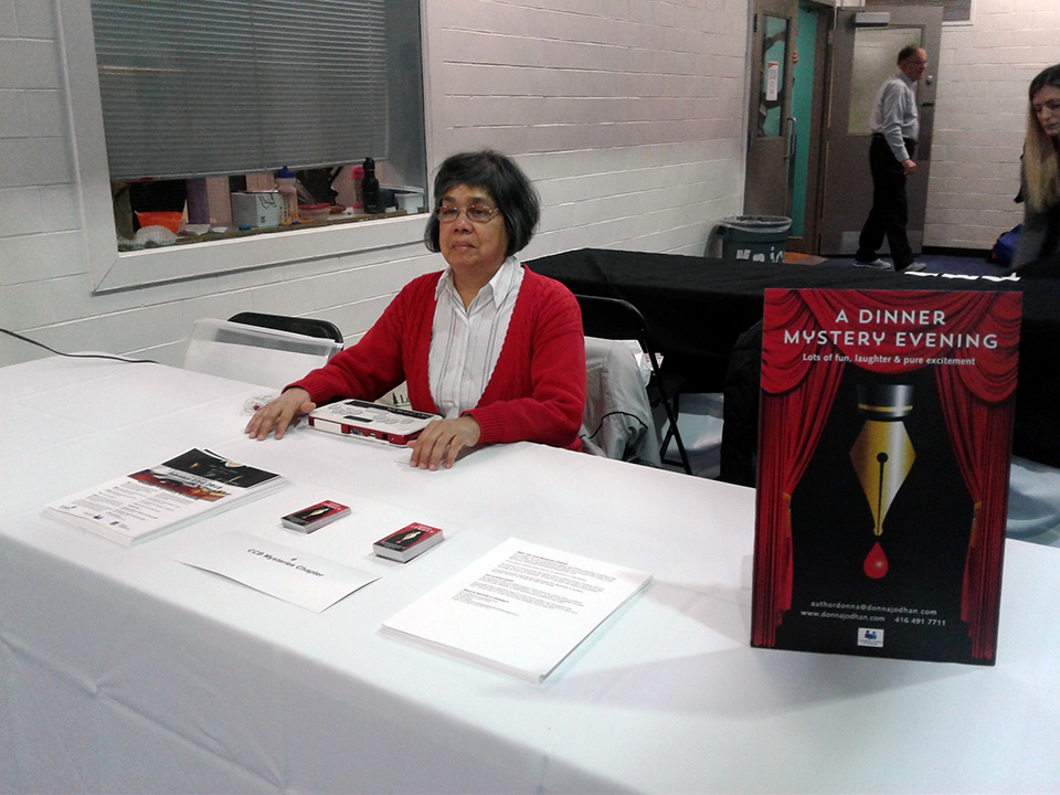 Photo of Donna Jodhan sitting at a table at the Expo 2018. On the table in front of her are fliers, cards, pamphlets, as well as a stand up sign announcing her Dinner Mystery Evenings.