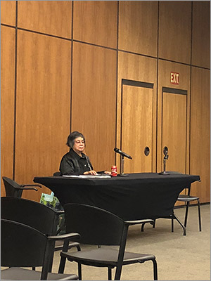Photo of Donna Jodhan sitting at a table in front of a microphone with an ear piece in.